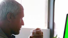 Mannelijk uitvoerend drinkwater terwijl het werken aan Desktoppc stock videobeelden