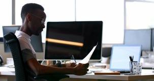 Mannelijk uitvoerend het controleren document bij bureau 4k stock video
