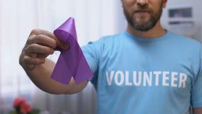 Mannelijk vrijwilligersholdings purper lint, epilepsie en alvleesklier- kankervoorlichting stock videobeelden