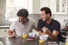 Mannelijk vrolijk paar die smartphone over ontbijt bekijken royalty-vrije stock foto's