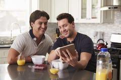 Mannelijk vrolijk paar die tabletcomputer bekijken over ontbijt royalty-vrije stock fotografie