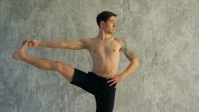 Mannelijk yoga hoofd het uitrekken zich been in de studio Status, die één been in de hand houden stock footage