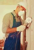Mannelijke aannemer die met boor in masker herstellen stock afbeeldingen