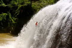 Mannelijke abseils massieve waterval Stock Foto's