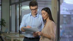 Mannelijke accountant die kosten bespreken met vrouwelijke directeur die van bedrijf documenten tonen stock footage