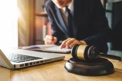 Mannelijke advocaat in het bureau met messingsschaal op houten lijst Rechtvaardigheid en wetsconcept in ochtendlicht royalty-vrije stock afbeelding