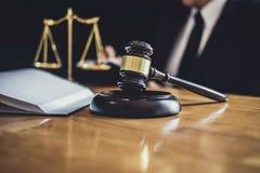 Mannelijke advocaat of rechter die met contractdocumenten, Wetsboeken en houten hamer aan lijst in rechtszaal, Rechtvaardigheidsa stock foto