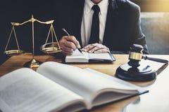 Mannelijke advocaat of rechter die met contractdocumenten, Wetsboeken en houten hamer aan lijst in rechtszaal, Rechtvaardigheidsa royalty-vrije stock afbeeldingen