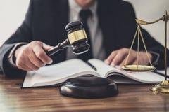 Mannelijke advocaat of rechter die met contractdocumenten, Wetsboeken en houten hamer aan lijst in rechtszaal, Rechtvaardigheidsa stock fotografie