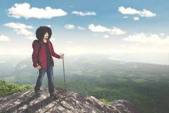 Mannelijke Afro-wandelaar die rots op heuvel beklimmen royalty-vrije stock afbeelding