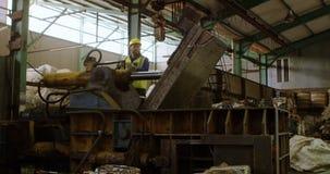 Mannelijke arbeider die aan machine in pakhuis 4k werken stock videobeelden
