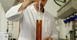 Mannelijke arbeider die alcoholische drank in metende cilinder 4k onderzoeken stock video