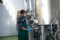 Mannelijke arbeider die bier van opslagtank nemen bij fabriek Stock Fotografie