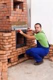 Mannelijke arbeider die een metselwerkverwarmer bouwen royalty-vrije stock foto