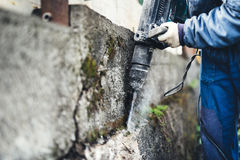 Mannelijke Arbeider die industrieel bouwhulpmiddel, industriële jackhammer met vernielingspuin en cement gebruiken Stock Afbeeldingen