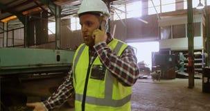 Mannelijke arbeider die op mobiele telefoon 4k spreken stock video