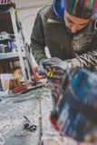 Mannelijke arbeider die Steen, rand het scherpen in de workshop van de skidienst herstellen, het glijden oppervlakte van de skis  stock afbeelding