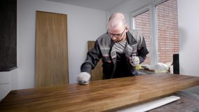 Mannelijke arbeider die zich in glazen en handschoenen bevinden die poetsmiddel op houten raad zetten stock video