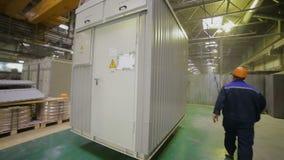 Mannelijke arbeiders bewegende container in een reusachtig pakhuis die industriële kraan met behulp van stock video