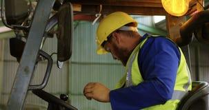 Mannelijke arbeiders werkende vorkheftruck in pakhuis 4k stock video