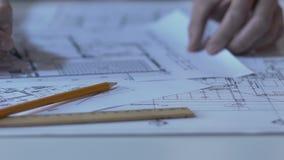 Mannelijke architect die de bouwlay-out controleren, die nota's en berekeningen, ontwerp maken stock videobeelden