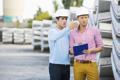 Mannelijke architecten die inventaris inspecteren bij plaats royalty-vrije stock foto's