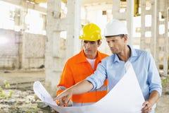 Mannelijke architecten die over blauwdruk bij bouwwerf bespreken Stock Foto's