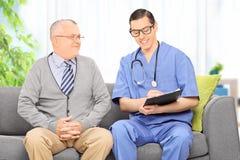 Mannelijke arts die aan een hogere patiënt spreken Royalty-vrije Stock Afbeelding