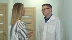 Mannelijke arts die aan jonge vrouwenpatiënt spreken in de het ziekenhuiszaal royalty-vrije stock fotografie