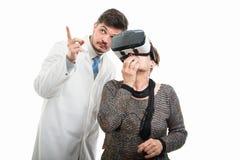 Mannelijke arts die aan vrouwelijke hogere patiënt met vrbeschermende brillen richten stock foto