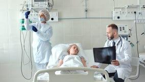 Mannelijke arts die aan vrouwelijke patiënt in het ziekenhuisbed spreken Verpleegster die een druppelbuisje voor zieke jonge vrou stock videobeelden