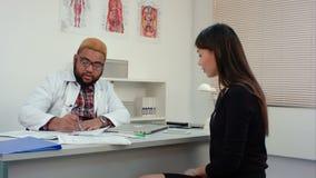 Mannelijke arts die aan vrouwelijke patiënt spreken en medische vorm invullen stock footage
