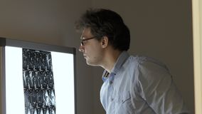 Mannelijke arts die computertomografieaftasten analyseren bij het scherm stock footage