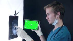 Mannelijke arts die een x-ray beeld onderzoeken, die groene het schermtablet gebruiken stock footage