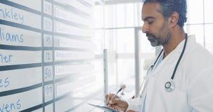 Mannelijke arts die informatieraad 4k controleren stock video