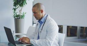 Mannelijke arts die laptop met behulp van bij bureau in bureau 4k stock video