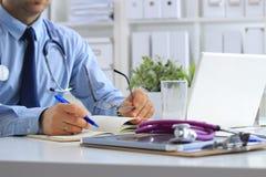 Mannelijke arts die laptop met behulp van, die bij zijn bureau zitten Stock Foto