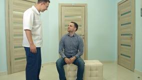 Mannelijke arts die mannelijke patiënt uitnodigen aan zijn bureau Royalty-vrije Stock Afbeeldingen