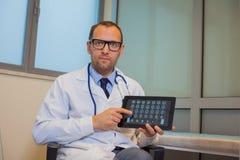 Mannelijke arts die met een tabletcomputer werken in zijn bureau. Hospit Stock Foto's