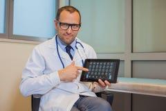 Mannelijke arts die met een tabletcomputer werken in zijn bureau. Hospit Stock Foto