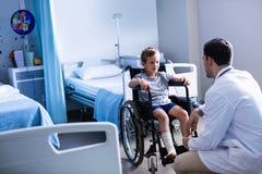 Mannelijke arts die met kindpatiënt interactie aangaan in afdeling stock foto