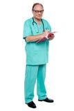 Mannelijke arts die in plichtsuren voorschrift schrijven Royalty-vrije Stock Afbeelding