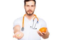 Mannelijke Arts die sinaasappel en pillen tonen stock foto