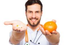 Mannelijke Arts die sinaasappel en pillen tonen royalty-vrije stock afbeeldingen