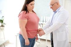 Mannelijke arts die taille van te zware vrouw meten stock foto's