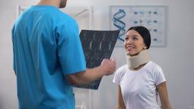 Mannelijke arts die vrouwelijke patiënt in goede x-ray resultaat van de schuim het cervicale kraag informeren stock video