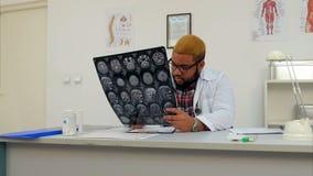 Mannelijke arts die zich over hersenen xray resultaten ongerust maken stock footage