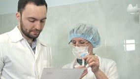 Mannelijke arts en verpleegster die bloedmonster bespreken stock foto's