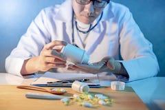 Mannelijke artsen gietende pillen van fles aan zijn hand stock afbeeldingen