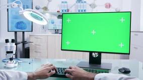 Mannelijke artsenhanden die aan computer van het prototype de groene scherm werken stock videobeelden